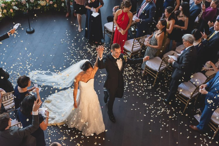 A bride and groom lifting their arms hand-in-hand in celebration as they exit their ceremony.