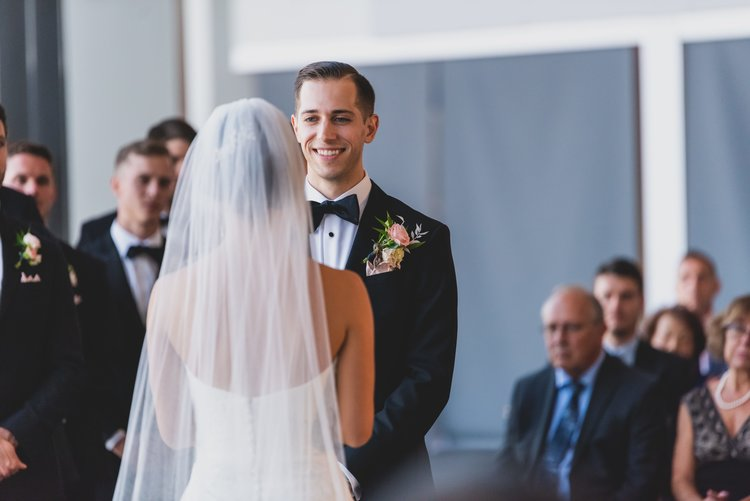 A groom in a black tuxedo smiling as his bride reads him her personalized wedding vows.