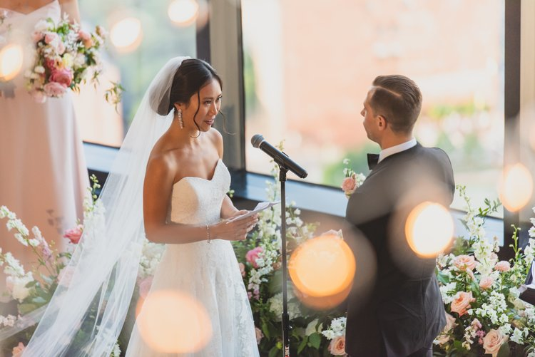 A bride reading her personalized wedding vows during the ceremony.