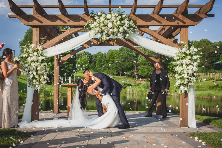 A groom dipping his new wife in a theatrical kiss the bride.