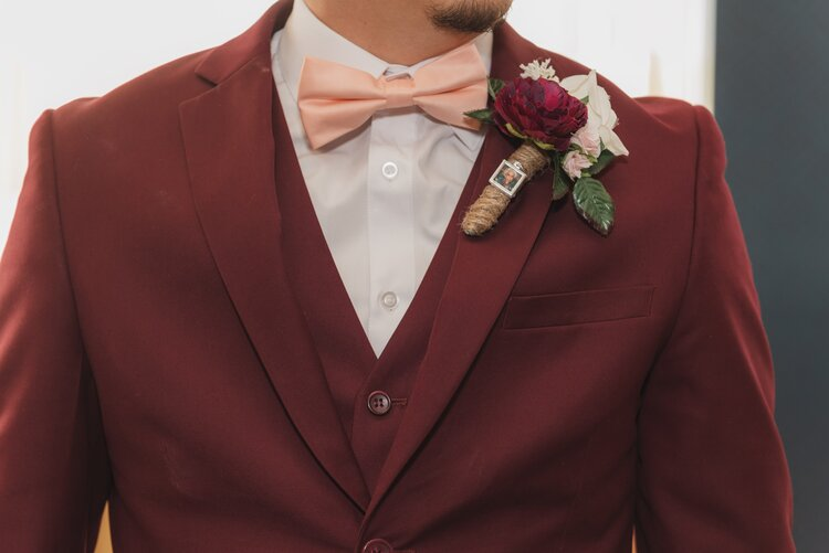 Groom wearing a deep red tuxedo, a pink bow tie and a boutonniere with twine shaped like a cigar.