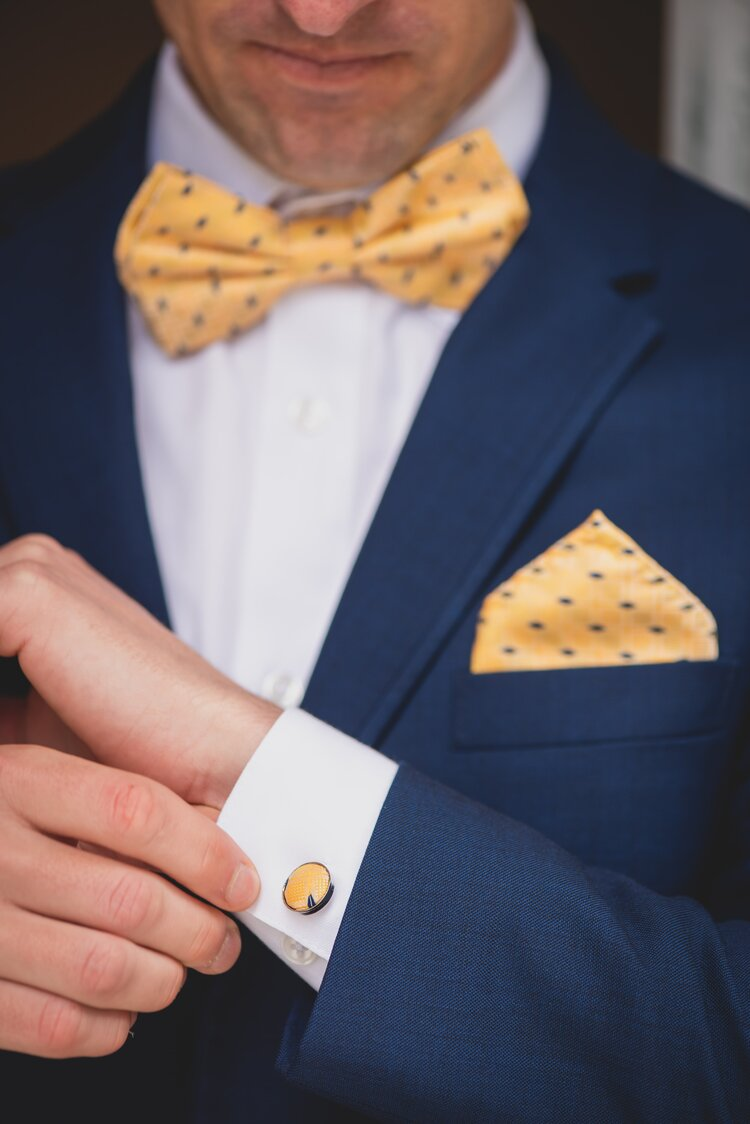 Groom in a navy tuxedo adjusting his sleeve, sporting gold cuff links.