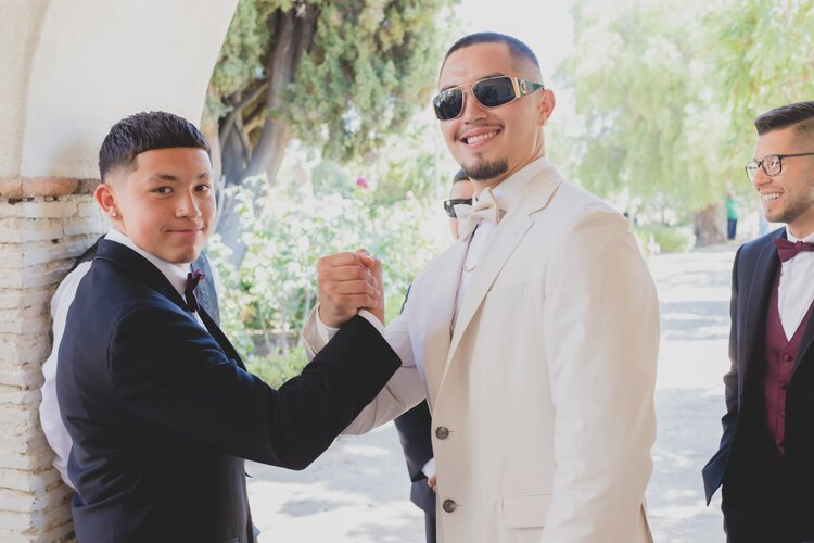 A stylish groom in cream colored tuxedo, high-fiving his best man.