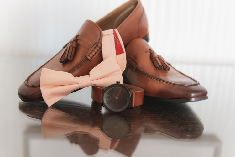 A stylish pair of brown wedding shoes, matching brown watch, and a pink bow tie.