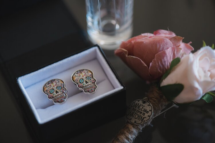 Skull shaped cuff links with bright blue eyes and a day of the day design.