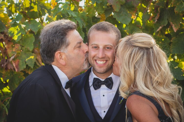 Parents of the groom kissing him on each cheek