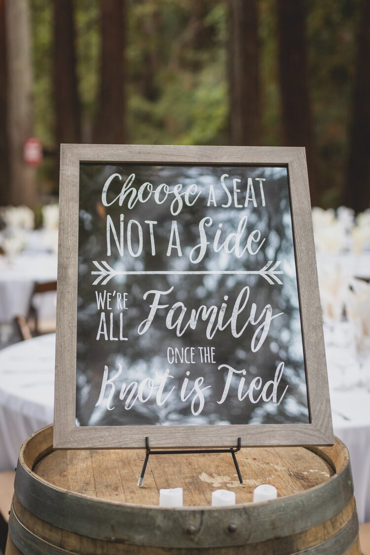 A DIY wedding sign on a wooden barrel.