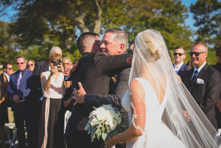 The groom hugging the father of the bride after the aisle walk