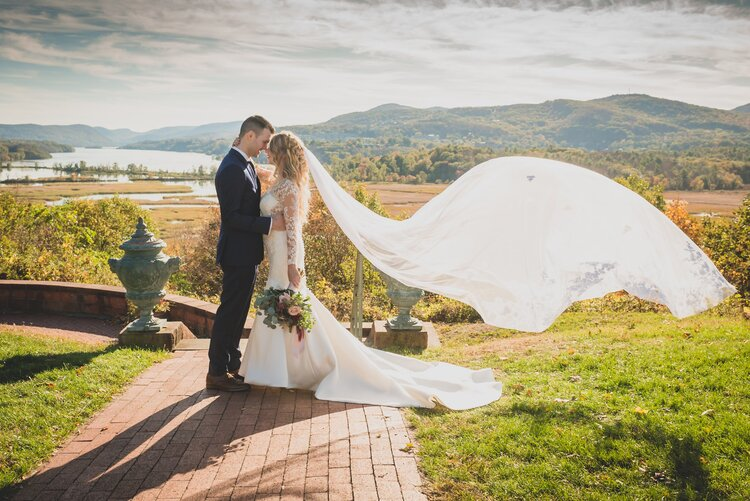 A groom and bride with her veil blowing in the wind behind them on an outdoor path in front of a gorgeous outdoor backdrop of rivers and rolling hills.