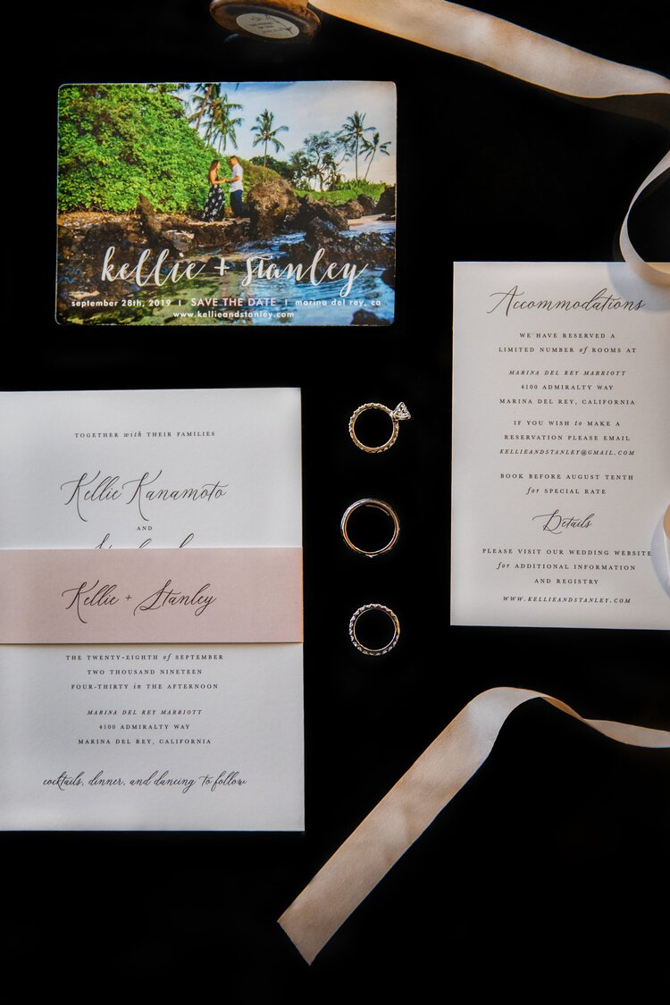 An wedding invitation suite and 3 rings on black velvet.