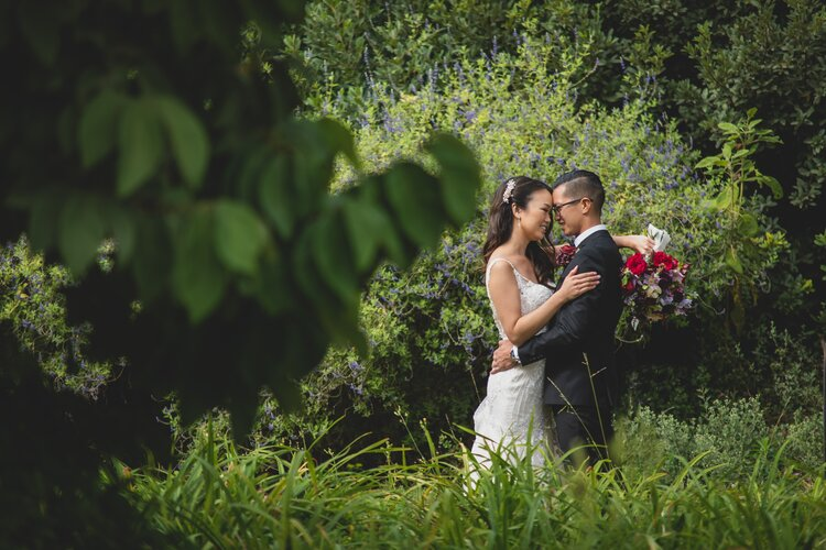 A newlywed couple in a lush green garden.