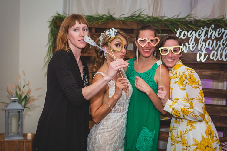 A bride and her guests taking selfies with their homemade wedding photo booth.