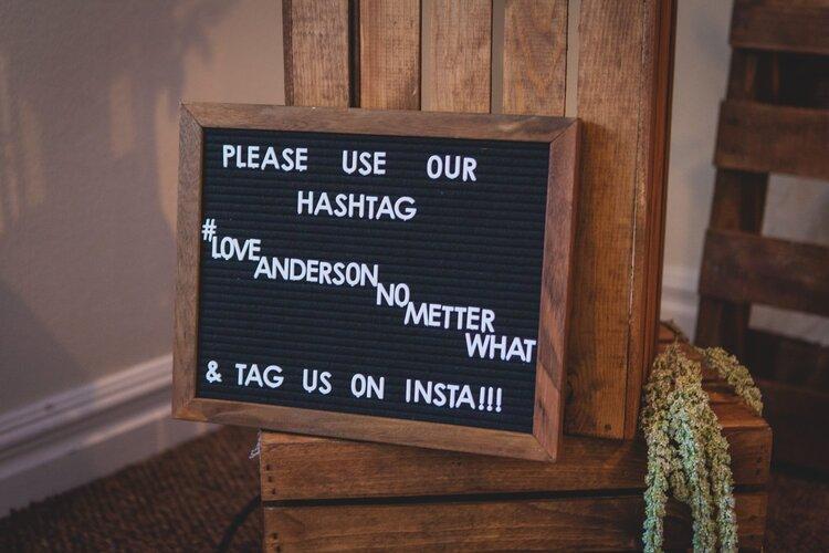 A DIY wedding sign displaying their wedding hashtag.