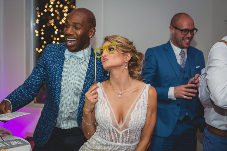 Bride with gold glasses as a photo booth prop.