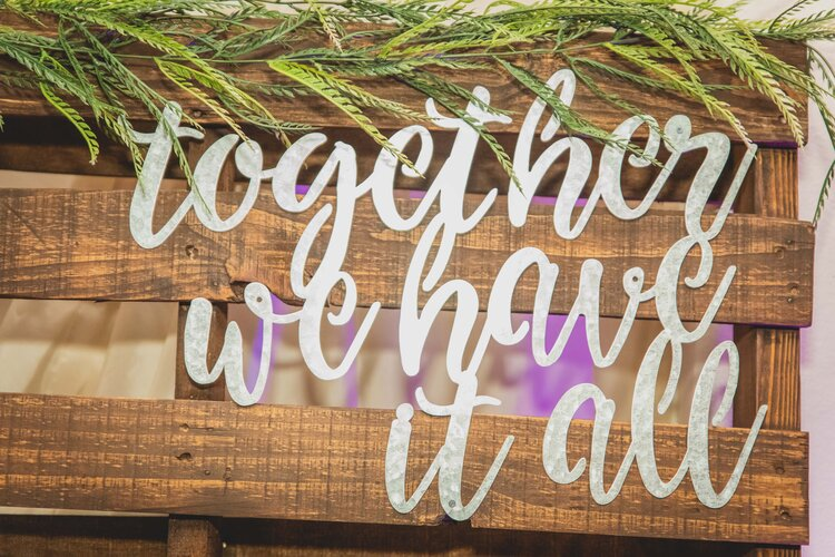 """Cursive letters on a wooden backdrop reading """"together we have it all."""""""