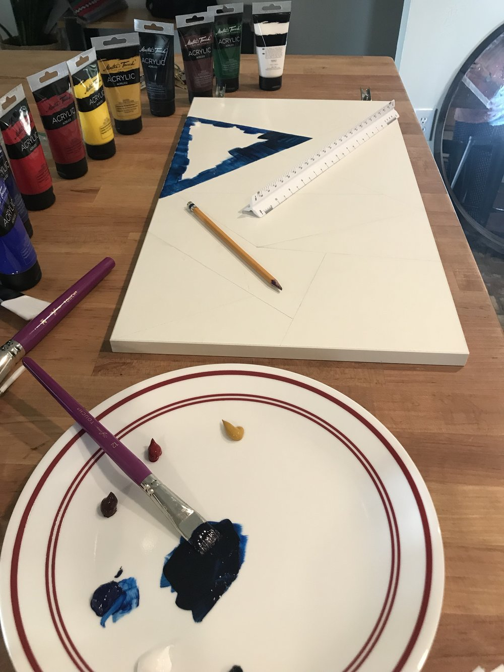 Here is my set up at the kitchen table. Yes, that is a dinner plate being used as a palette. I used acrylic paints. They are water based so no harm was done to dinner plates during this DIY project. I purchased the paints at Hobby Lobby on sale 40% off. I think you can go any day of the year and their craft supplies will be on sale. But nonetheless it's exciting to think you are there on a special sale day. Leave me to my bliss.  My design is simple. Not much thought went into it. I used a #2 pencil and a straight edge to make geometric designs. Keep in mind the smaller the shapes the more precise painting you will have to do. If this is in your comfort zone then by all means make small shapes. Personally it was out of my comfort zone. Especially since I rarely paint, except for walls and floors.