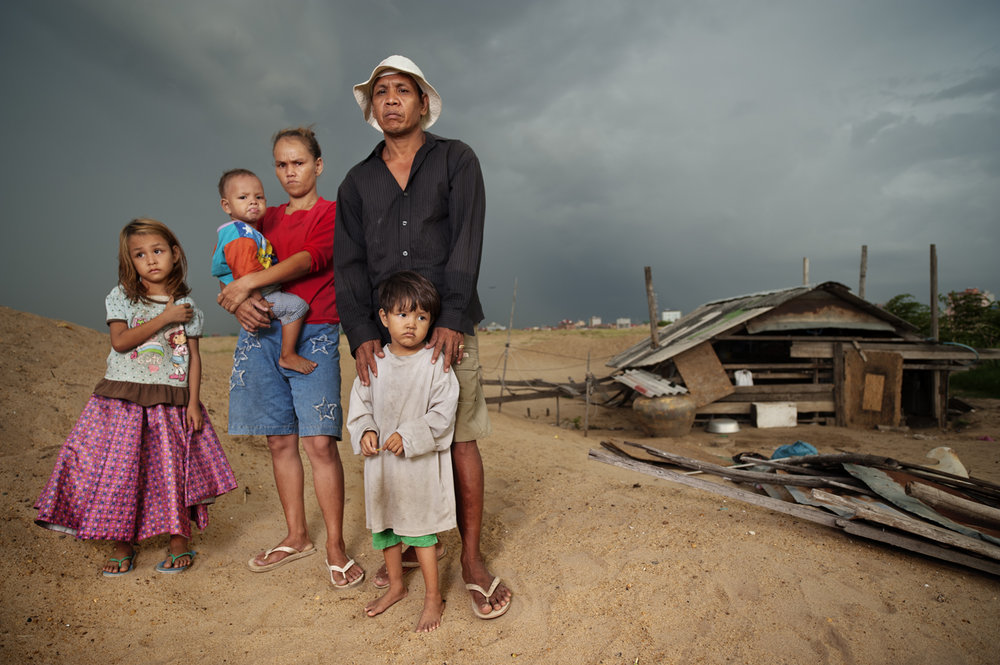 A family stands in front of their house, which is the only house left from an entire community. The family opposes the government's demands for forced relocation ( land grabbing ), Boeung Kak lake, Phnom Penh / Cambodia