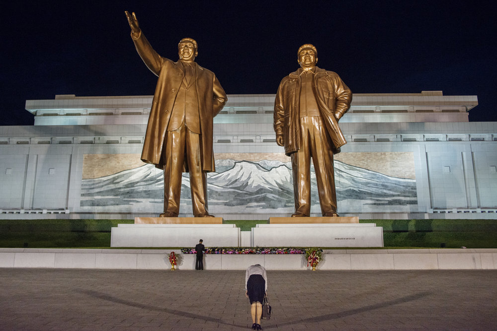 A woman bowing infront of the statues of the deceased leaders Kim il-sung and Kim Jong-il, Pyongyang / North Korea - 2013