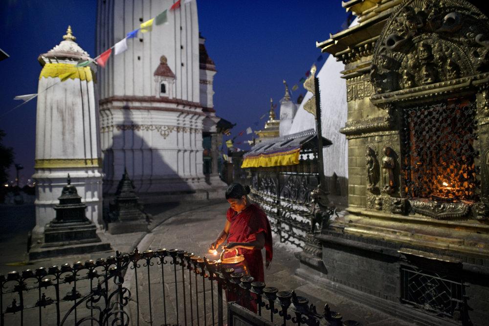 Women lighting candles at Swayambhunath Buddhist stupa, Kathmandu/ Nepal