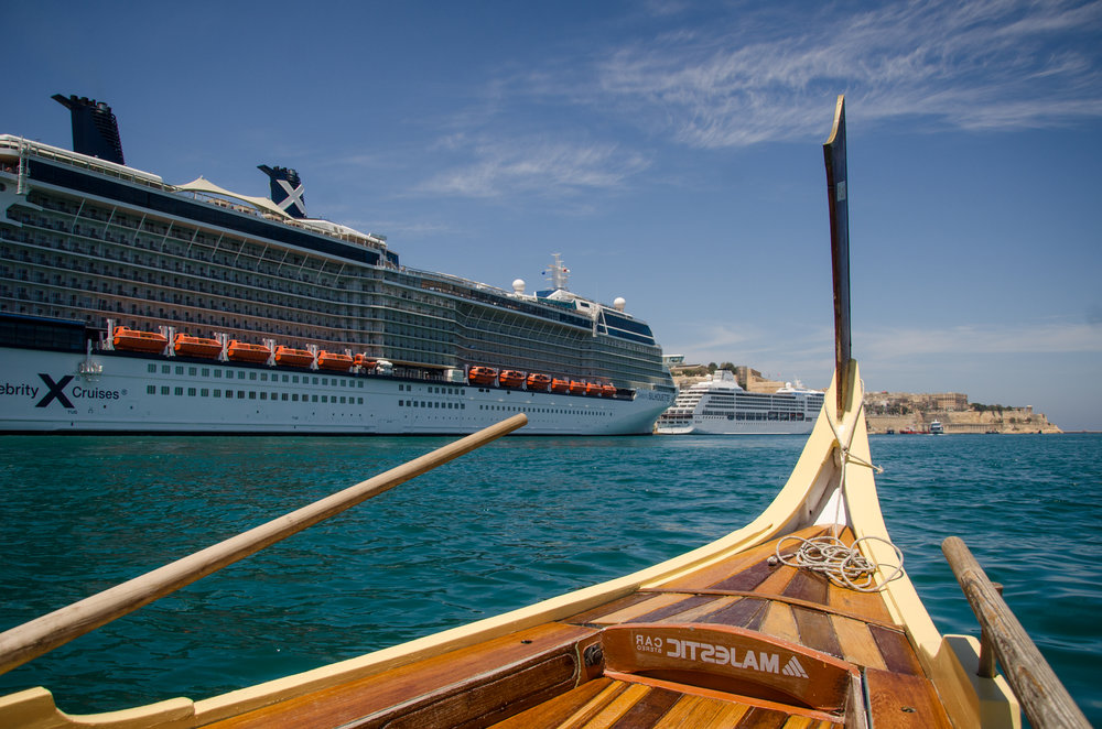 An authentic maltese boat in the grand harbour, cruise liner in background.