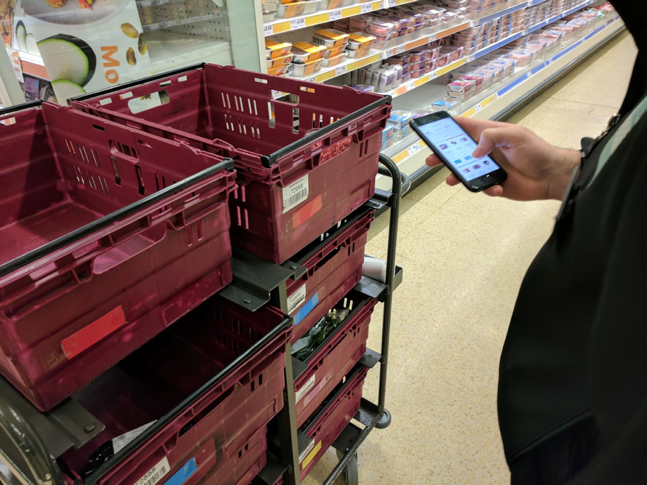 Colleague using the prototype in store with makeshift colour coded boxes