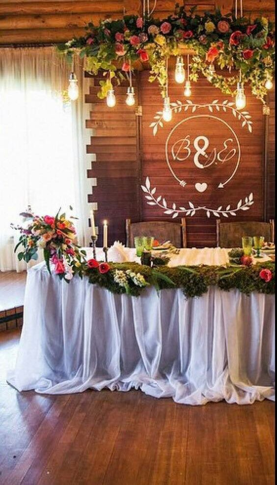 Woody Forest & Lights - Wooden chairs, draped garland of flowers, initials, and simple hanging bulb lights.