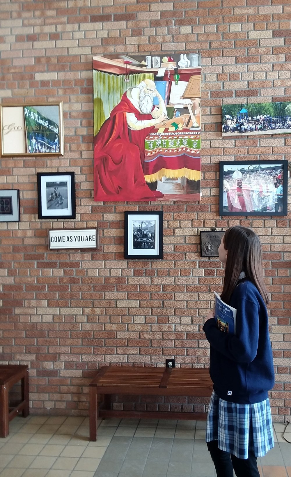 - A seventh-grader pauses in front of an image of St. Jerome in his study.