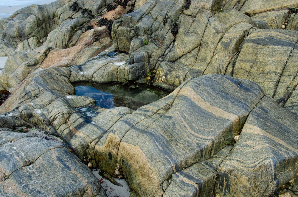 Rocks pouring over the Maze beach