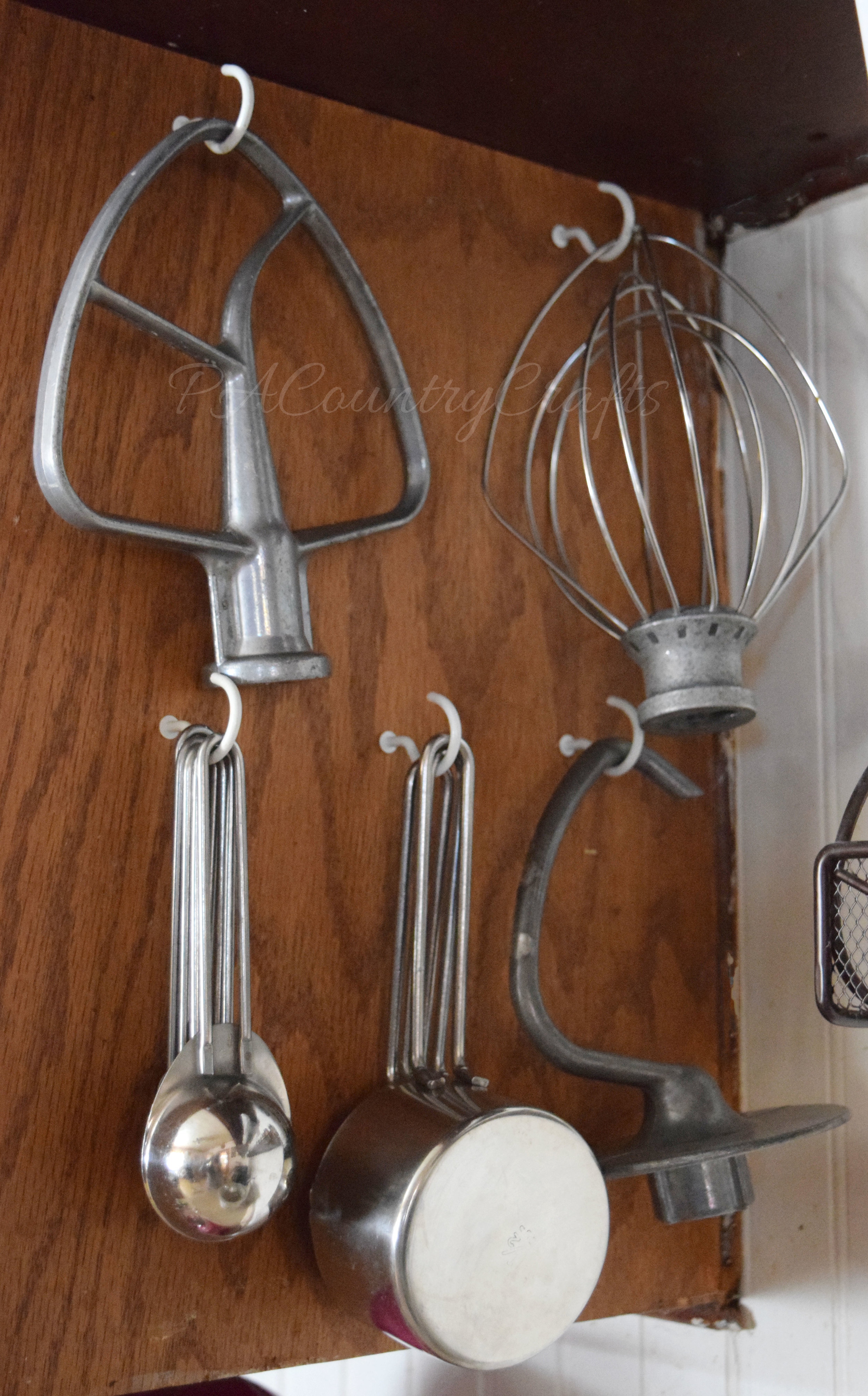 Hang mixer attachments and measuring cups from hooks on the side of a cupboard.
