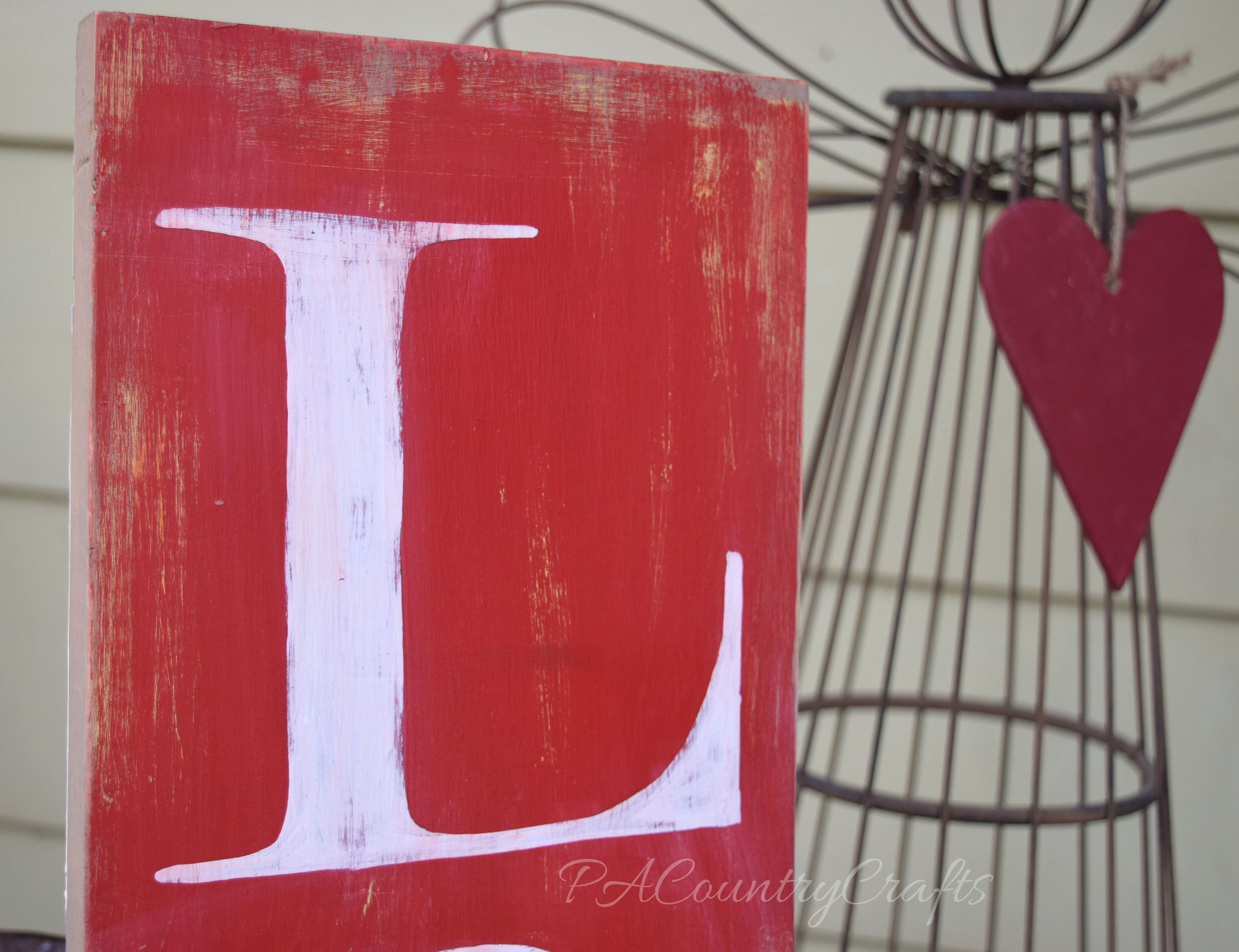 rustic painted letter L on red and white sign