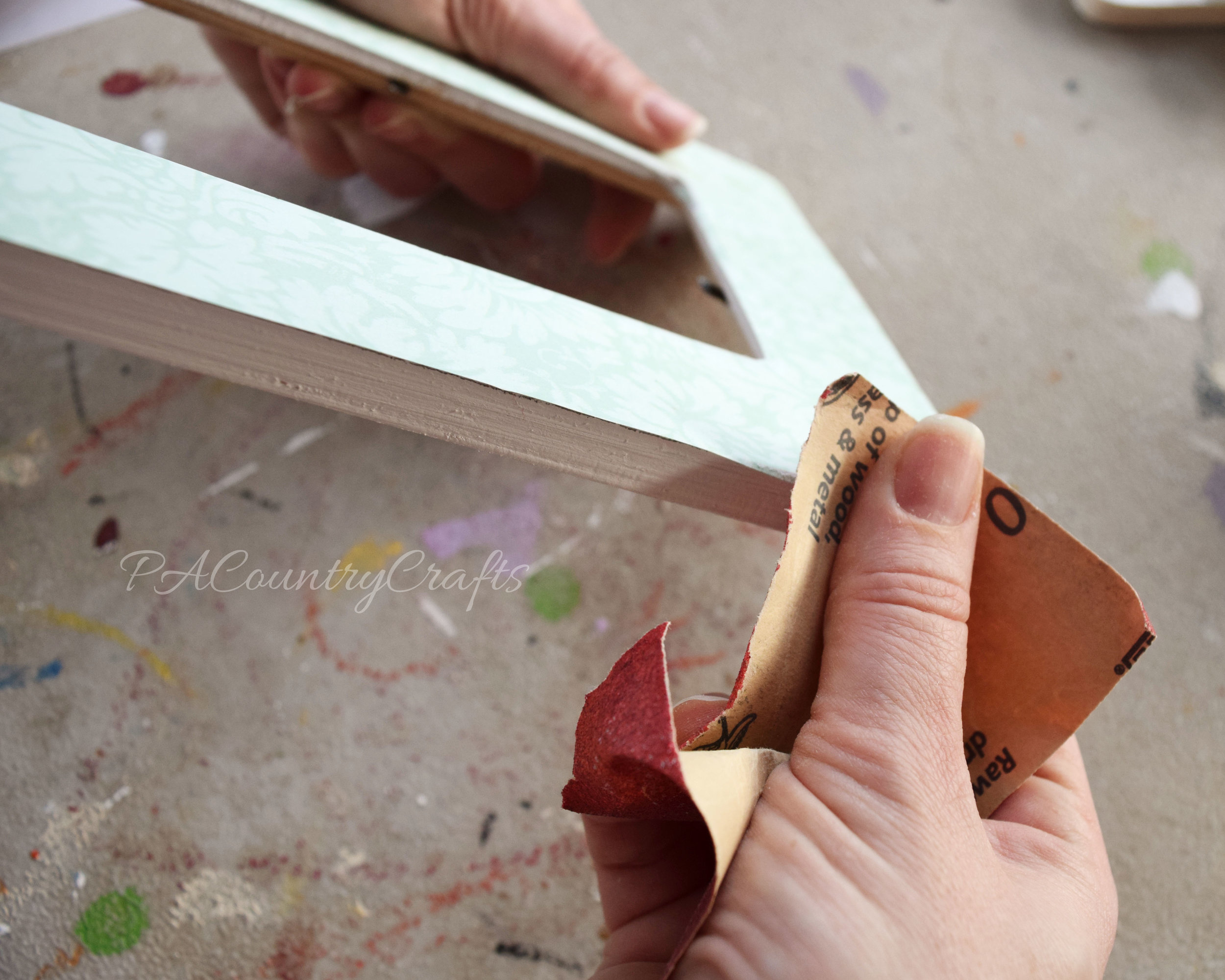 This tip helps you sand extra paper of the edges of mod podge frames for a clean finish.