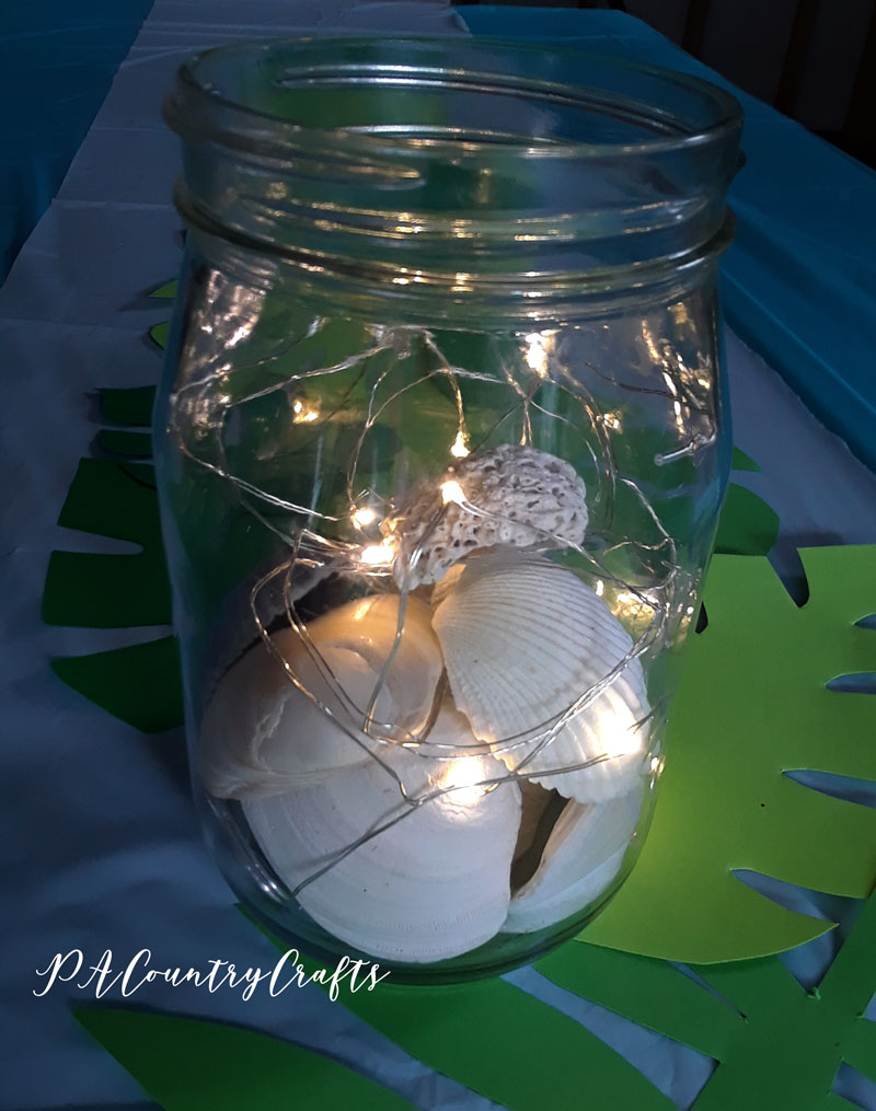 Seashells and fairy lights as a beach themed centerpiece!