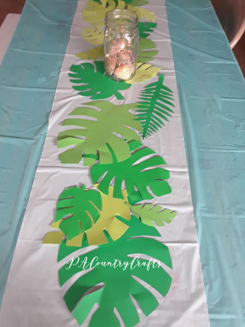 Easy decorations for a beach birthday party or tropical luau... cut out leaves from cardstock as a table runner.