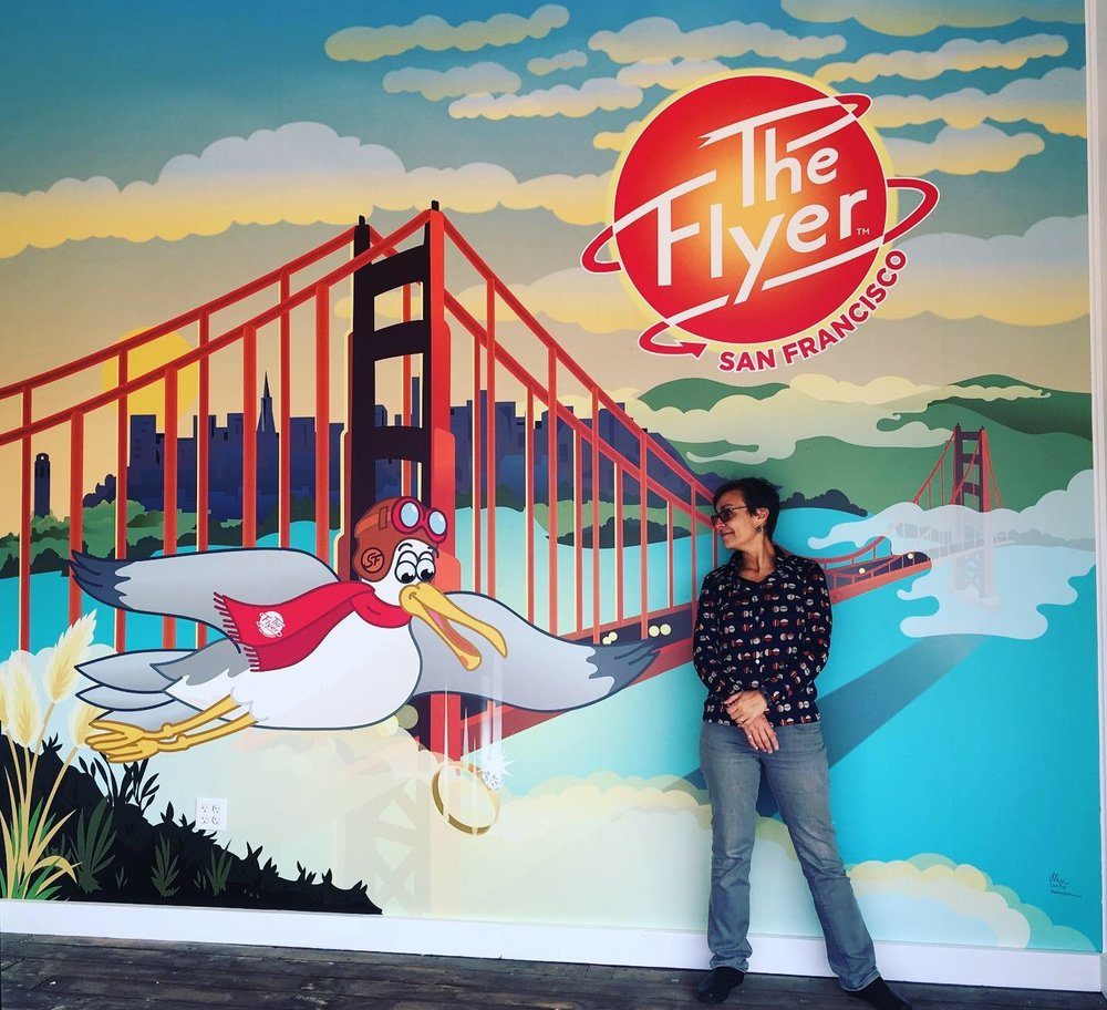 That's me, standing in front of the digital illustration mural I created for the entryway of Pier 39's The Flyer—San Francisco attraction.