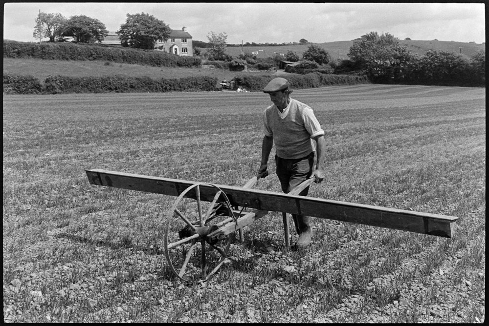 Farmer using old seed drill. Beaford, Balls Farm, June 1975. Documentary photograph by James Ravilious for the Beaford Archive © Beaford Arts