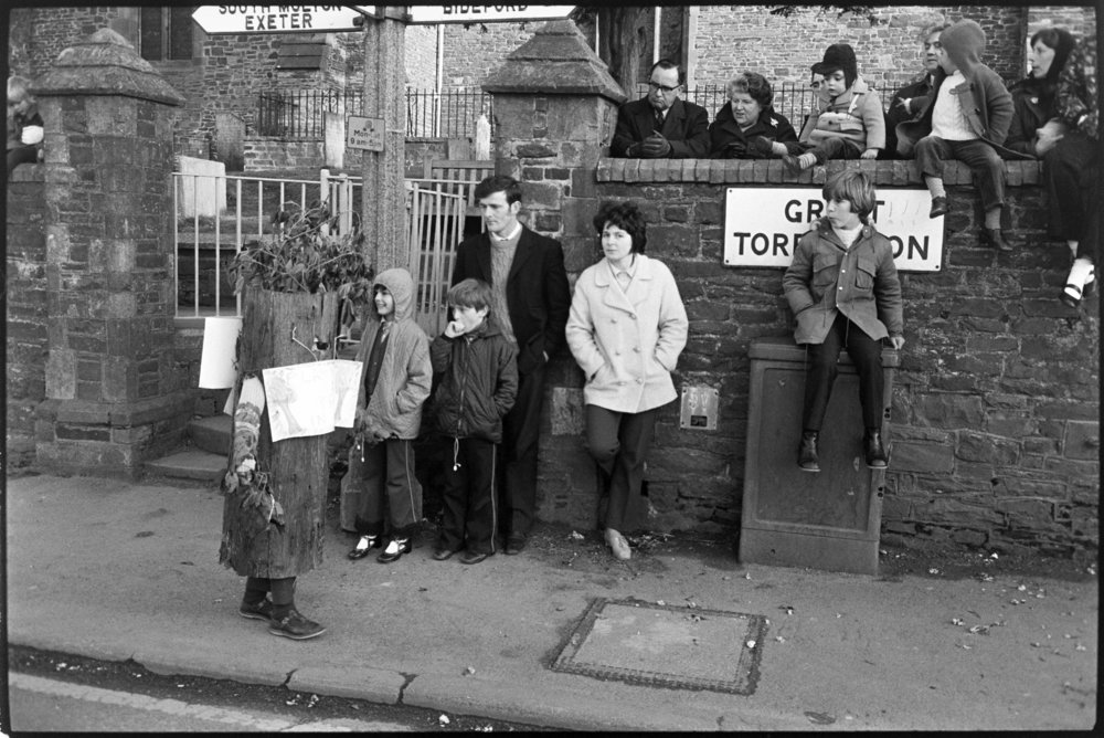 Spectators watch parade.  Child dressed as a tree, Torrington, 5 May 1973
