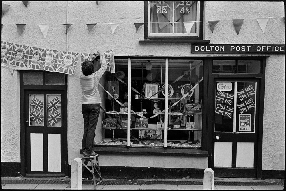 Woman decorating Post Office with flags on Jubilee day, Dolton, Post Office, 6 June 1977