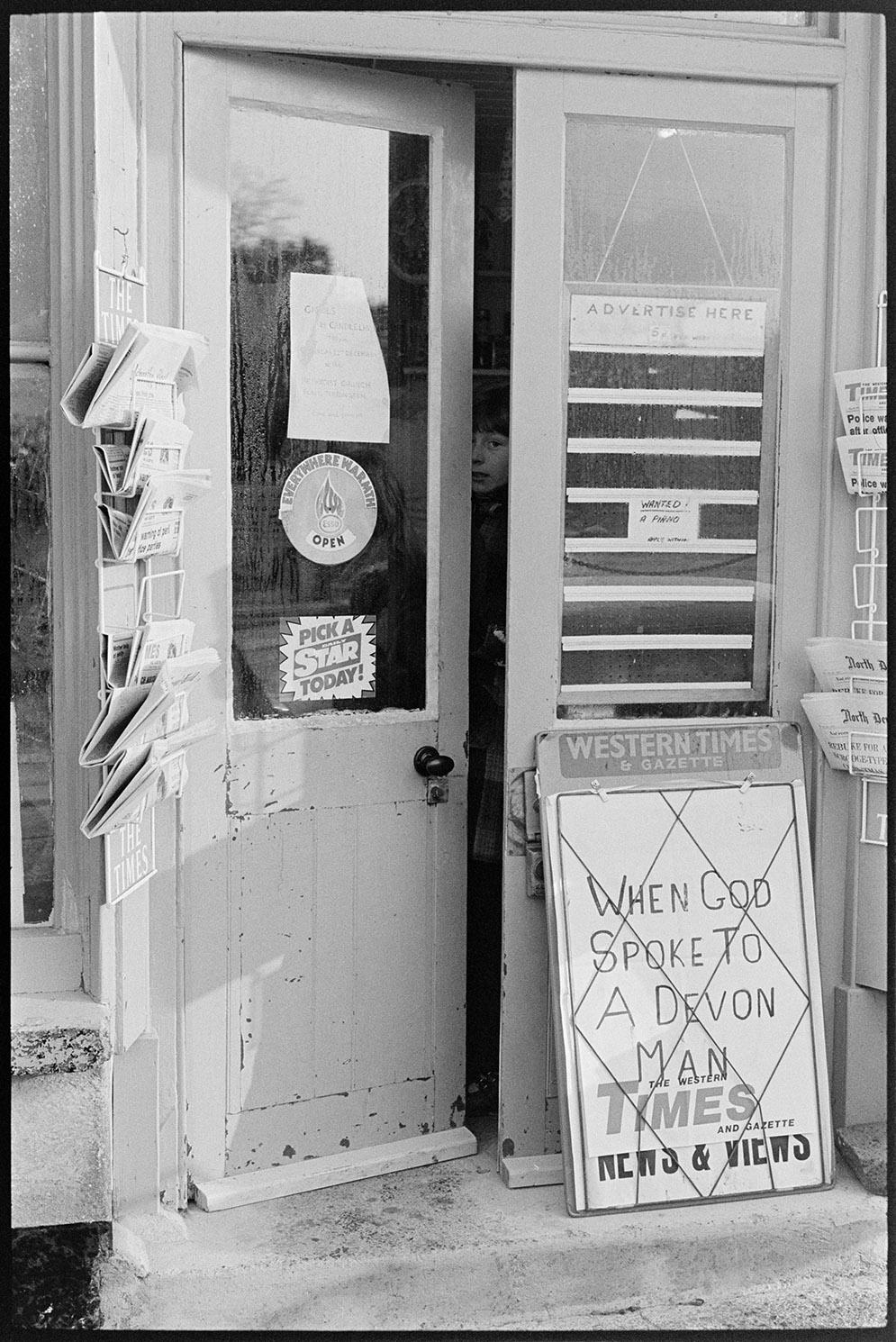 Front of shop with newspaper hoarding, Black Torrington, December 1979