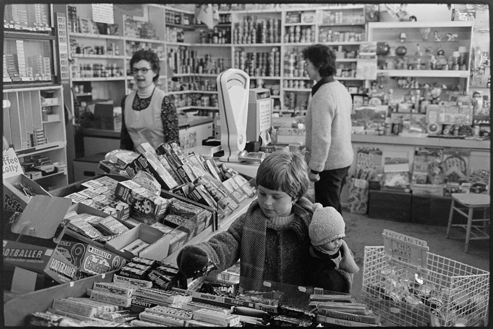 Interior of village grocery stores with customers, child buying sweets, Black Torrington, December 1979