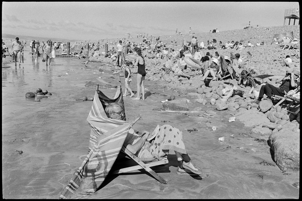 Man in deckchair sheltering from wind on crowded beach,Westward Ho!,August 1981