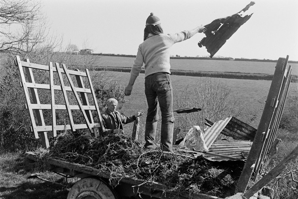 Throwing old corrugated iron sheets into field / scrubland, Beaford, March 1972