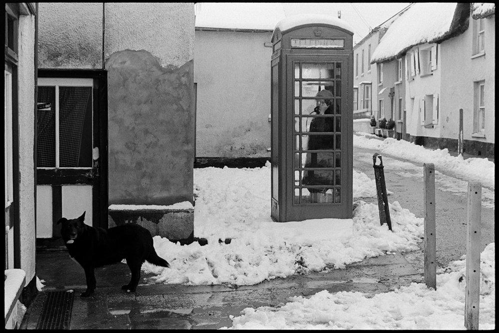 Woman in phone box talking on phone. Documentary photograph by James Ravilious for the Beaford Archive, Beaford Arts