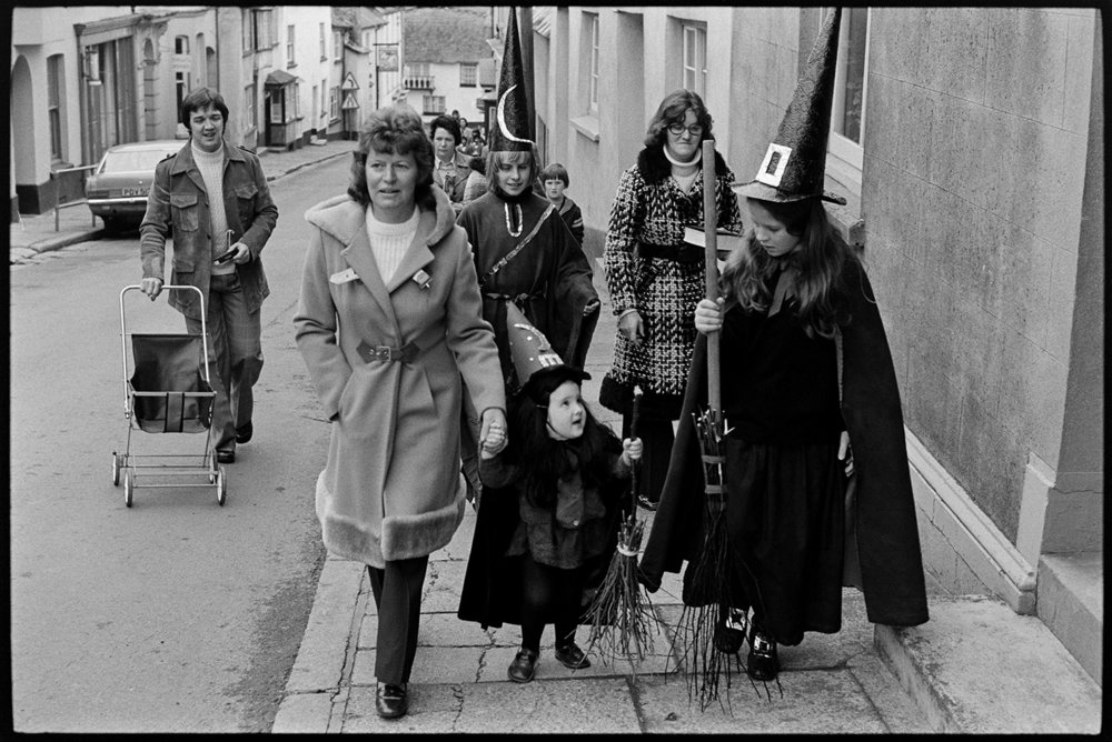 Girls dressed as witches and walking up the street, Hatherleigh, November 1975