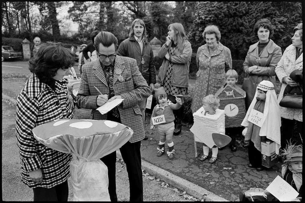 Man taking people's names for fancy dress competition, Hatherleigh, November 1975