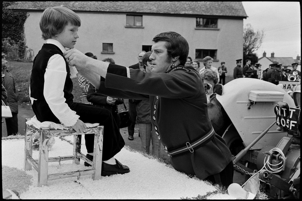 Bandsman adjusting young boy's outfit in carnival parade, Hatherleigh, November 1975