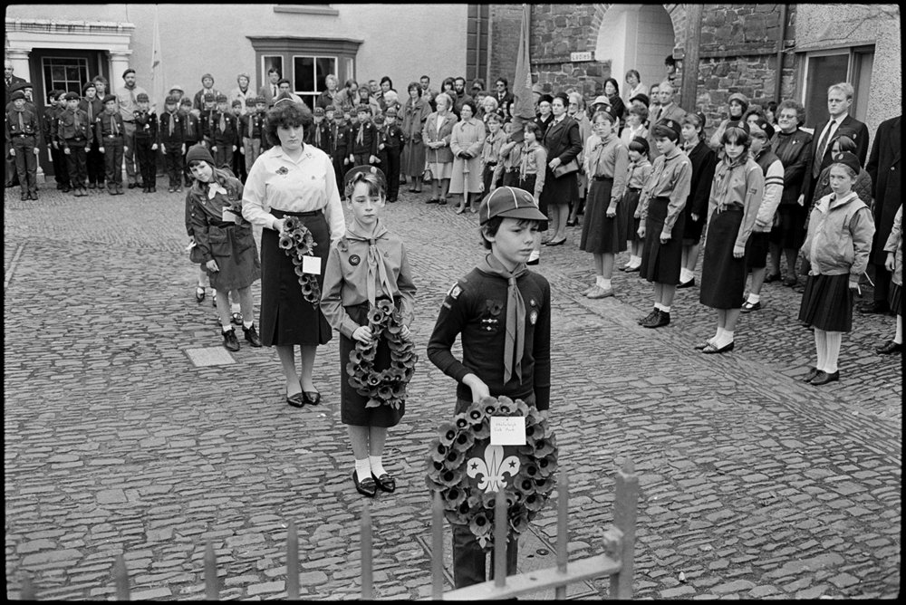 Parade at Memorial, laying wreaths by scouts, brownies & guides.  Chulmleigh, November 1987.