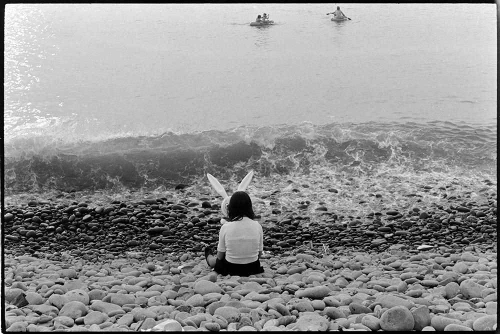 Girl on beach with rabbit 'mask', Westward-Ho!, August 1973. Documentary photograph by James Ravilious