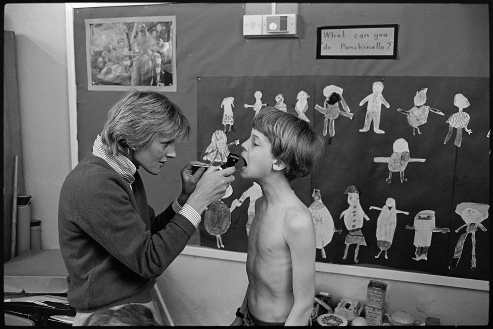 Nurse giving children medical inspection in school, Dolton 1985. Documentary photograph by James Ravilious for the Beaford Archive.