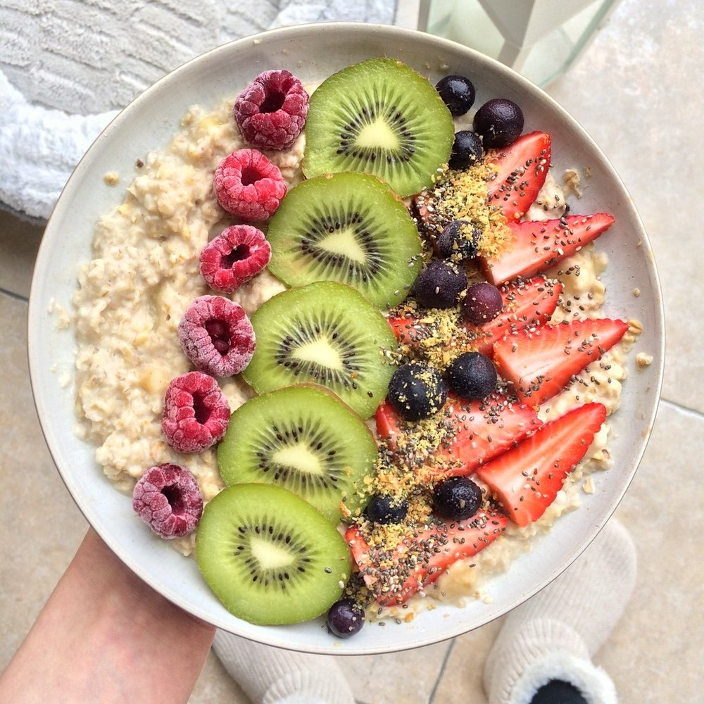 Banana porridge decorated with a sliced kiwi, strawberries, frozen raspberries, blueberries, flax and chia seeds.