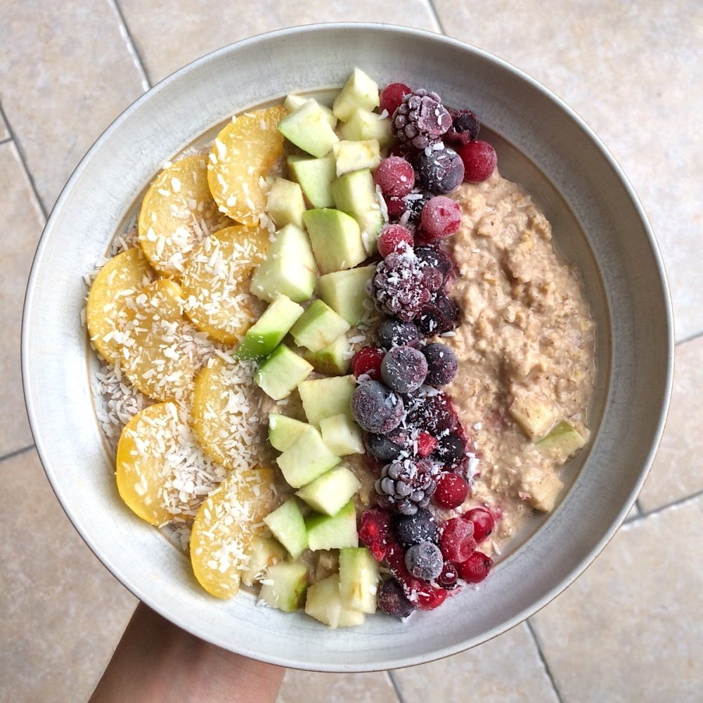 Cinnamon-spiced apple porridge loaded up with a sliced yellow plum, diced apple, mixture of frozen berries and shredded coconut.